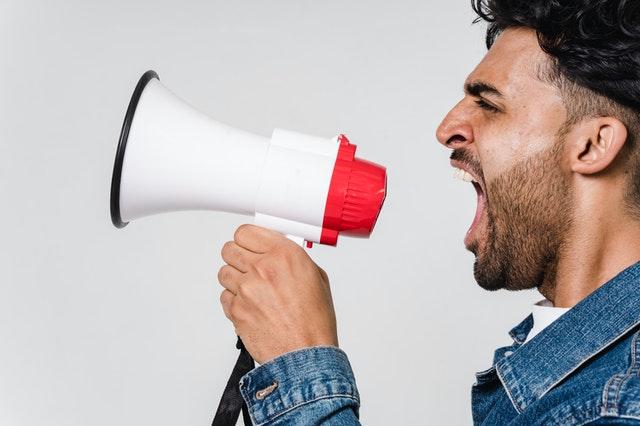 homme criant dans un speaker pour parler de la radio